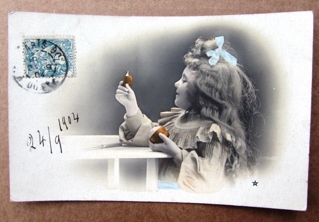 Девочка за столом чистит апельсин Штемпель 1904