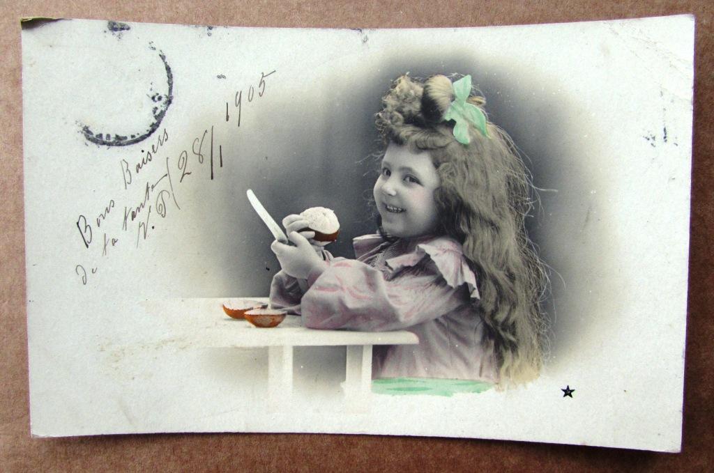 Девочка за столом с ножом чистит апельсин Штемпель 1905
